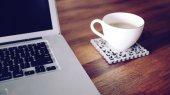 Laptop i filiżanka kawy na stole